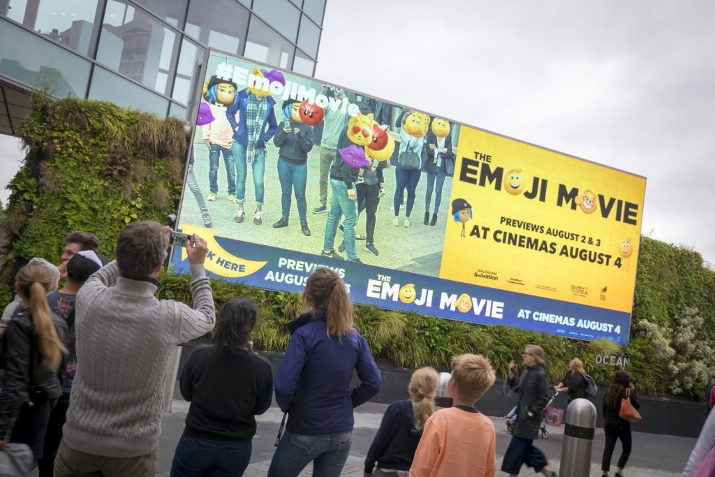 People crowd to look at The Emoji Movie's interactive campaign on Ocean's Eat Street screen.